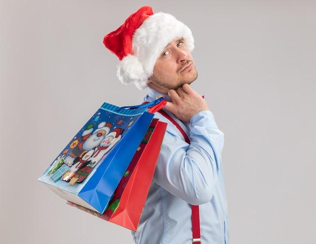 Giovane uomo che indossa bretelle farfallino in cappello di babbo natale che tiene sacchetti di carta regalo guardando la fotocamera con espressione triste in piedi su sfondo bianco