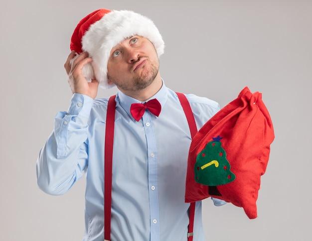 Giovane uomo che indossa bretelle farfallino in cappello di babbo natale che tiene la borsa di babbo natale piena di regali guardando perplesso in piedi su sfondo bianco