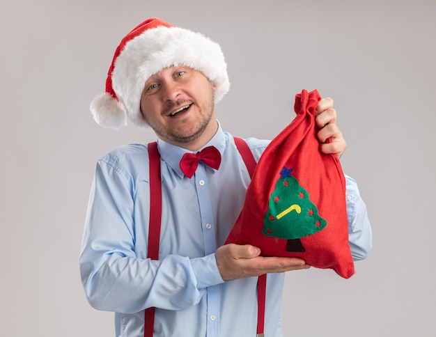 Young man wearing suspenders bow tie in santa hat showing red santa claus bag full of gifts looking at camera happy and cheerful smiling standing over white background