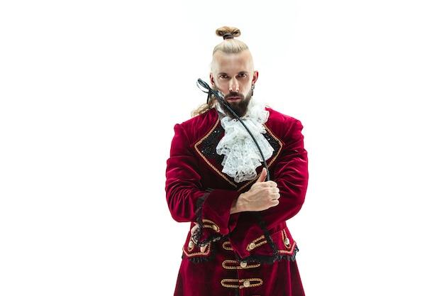 Il giovane che indossa un costume medievale tradizionale del marchese che propone allo studio con la frusta