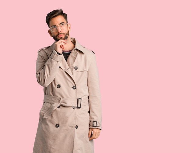 Young man wearing trench coat doubting and confused
