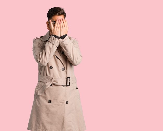 Young man wearing trench coat feels worried and scared