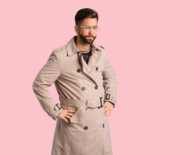Young man wearing trench coat scolding someone very angry