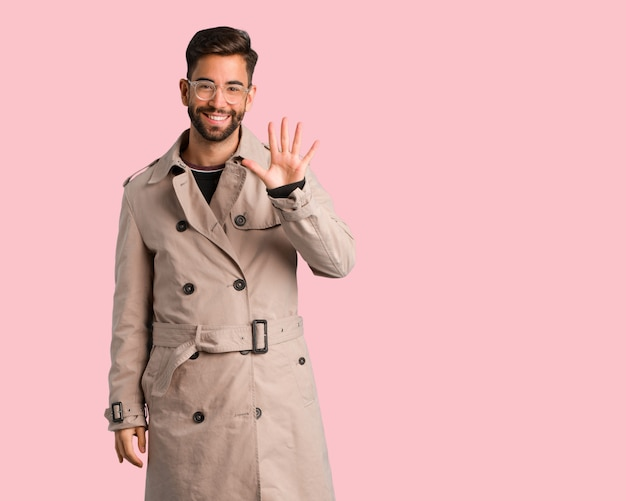 Young man wearing trench coat showing number five