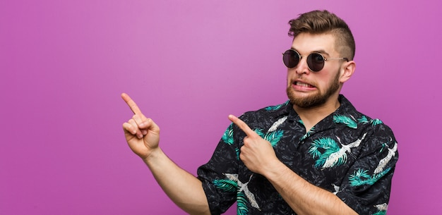 Young man wearing a vacation look shocked pointing with index fingers to a copy space.