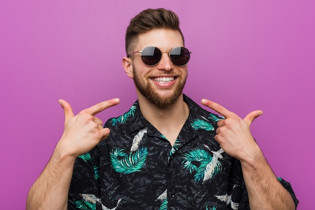 Young man wearing a vacation look smiles, pointing fingers at mouth.