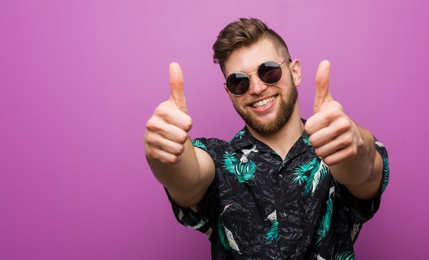 Young man wearing a vacation look with thumbs ups, cheers about something, support and respect concept.