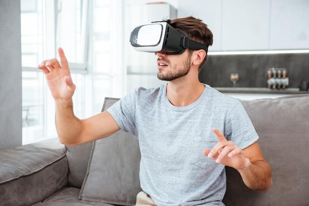 Молодой человек в устройстве виртуальной реальности, сидя на диване