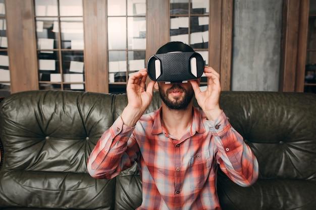 Молодой человек в очках виртуальной реальности дома.
