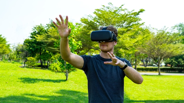Young man wearing virtual reality glasses and gesturing in the park