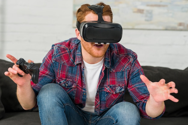 Young man wearing virtual reality glasses holding joystick in hand playing video game
