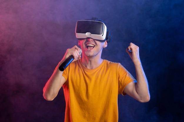 Молодой человек в гарнитуре виртуальной реальности и держит микрофон на темно-синей поверхности