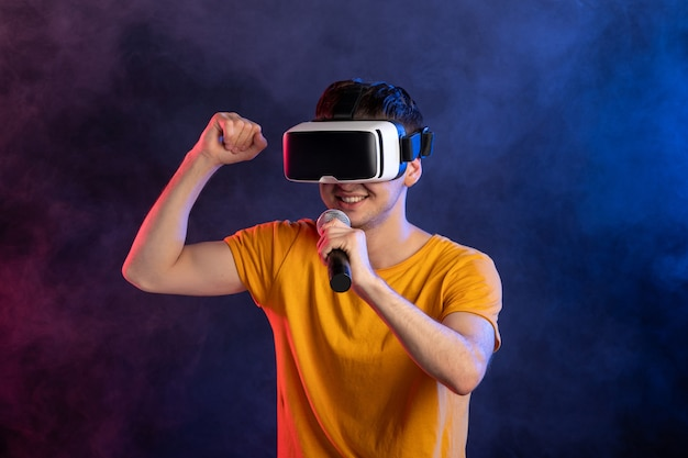 バーチャルリアリティヘッドセットを着用し、紺色の表面を歌う若い男