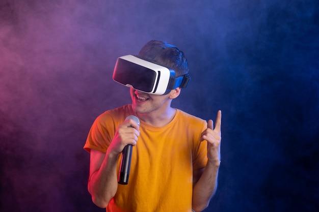 Giovane uomo che indossa le cuffie da realtà virtuale e tenendo il microfono superficie blu scuro