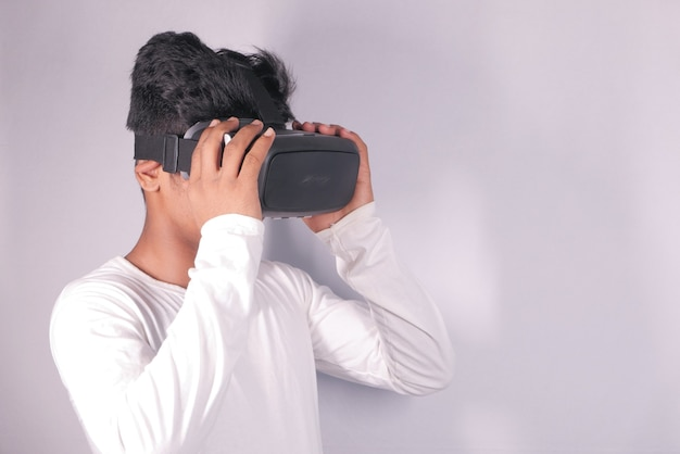 バーチャルリアリティヘッドセット、白で隔離のvrボックスを身に着けている若い男