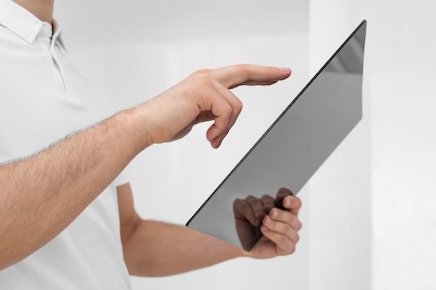 Young man wearing white clothes using tablet close up