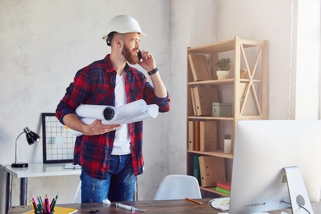 흰색 헬멧을 쓰고 사무실에서 시선을 돌리면서 스마트폰 통화를 하는 젊은 남자. 엔지니어링 및 건축 개념