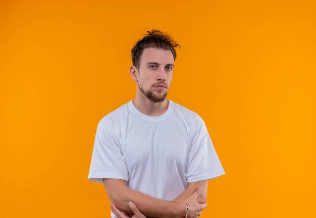 孤立したオレンジ色の壁に手を交差させる白いtシャツを着て若い男