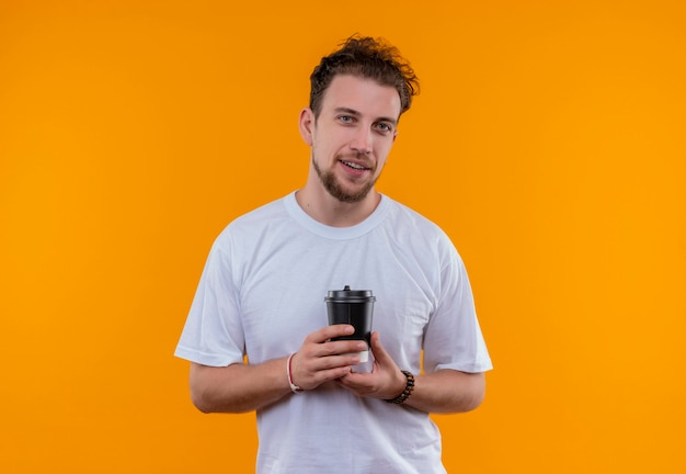 孤立したオレンジ色の壁にコーヒーのカップを保持している白いtシャツを着て若い男