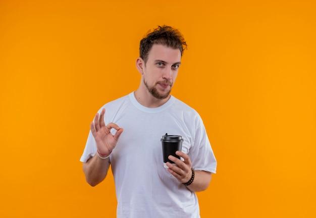 격리 된 주황색 벽에 좋아요 제스처를 보여주는 커피 잔을 들고 흰색 티셔츠를 입고 젊은 남자