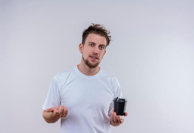 격리 된 흰 벽에 제스처를 보여주는 커피 한잔 들고 흰색 티셔츠를 입고 젊은 남자