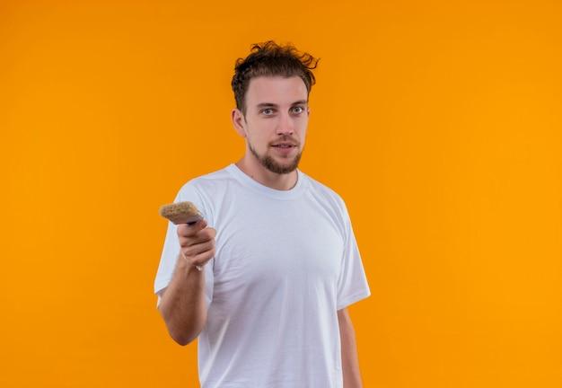 Молодой человек в белой футболке протягивает кисть на изолированной оранжевой стене