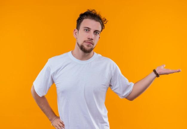 Giovane uomo che indossa la maglietta bianca punta a lato mise la mano sul fianco sul muro arancione isolato