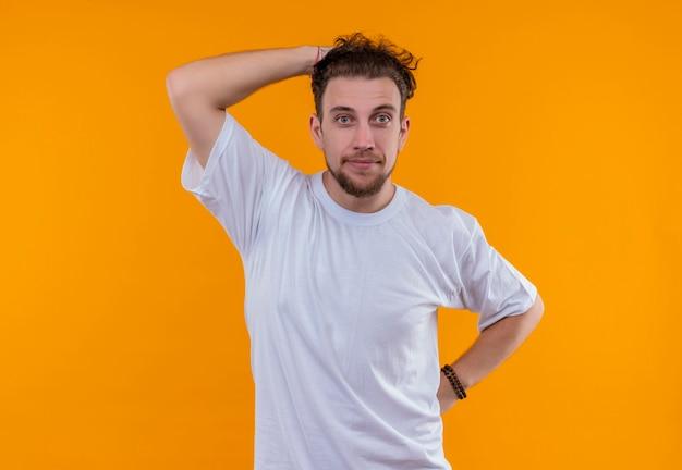 Giovane uomo che indossa la maglietta bianca mise la mano sulla testa sul muro arancione isolato