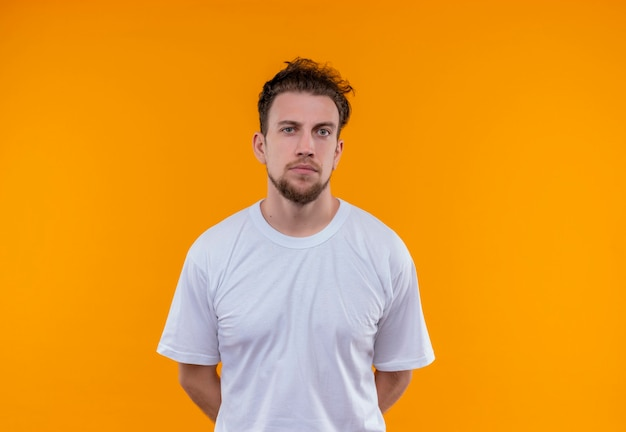 Young man wearing white t-shirt put his hands on back on isolated orange wall
