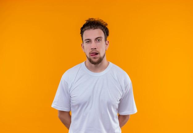 Giovane uomo che indossa la maglietta bianca mise le mani sulla schiena e mostrando la lingua sul muro arancione isolato
