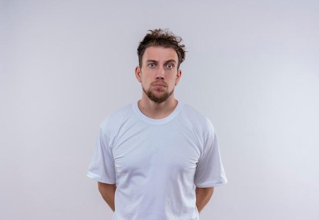 白いtシャツを着た若い男は、孤立した白い壁に手を置く