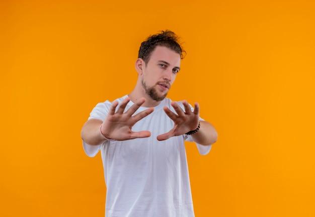 격리 된 주황색 벽에 중지 제스처를 보여주는 흰색 티셔츠를 입고 젊은 남자