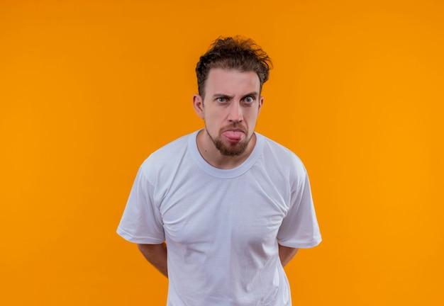 Молодой человек в белой футболке показывает язык на изолированной оранжевой стене