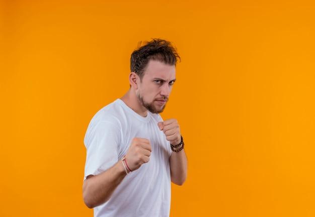 Giovane che indossa la maglietta bianca in piedi nella posa di combattimento sul muro arancione isolato