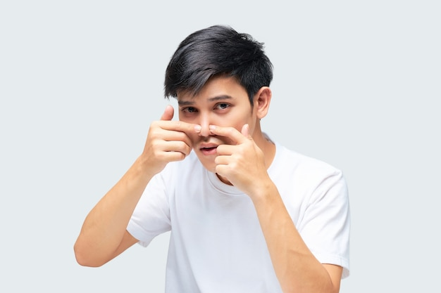 Young man wearing a white tshirt using his hand squeezed a pimple on the tip of his nose.