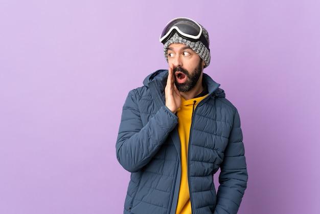 孤立した紫色の背景に冬のスポーツを着ている若い男