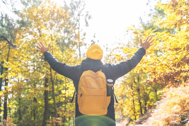 Молодой человек носить желтый рюкзак руки вверх в природе. человек, идущий в горы.