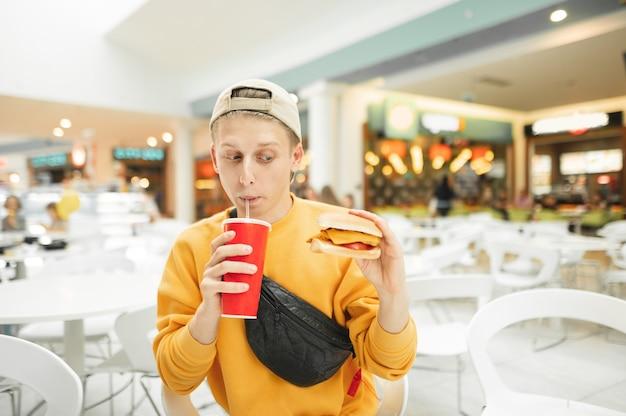 冷たいさわやかなドリンクを飲みながら、黄色の服とライトキャップを身に着けている若い男