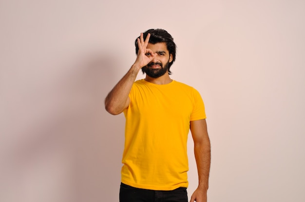 黄色のtシャツを着て、指を通して見ている目の笑顔の手で大丈夫ジェスチャーをしている若い男
