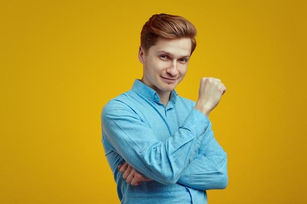 Молодой человек в синей рубашке позирует в студии на желтом фоне