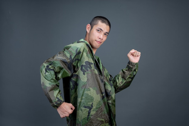 The young man wears a camouflage raincoat and shows different gestures.