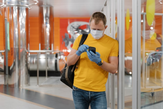 Young man wears surgical mask and gloves, uses smartphone, types on screen, poses with rucksack, prevents coronavirus