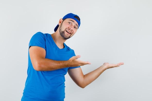 환영 또는 파란색 티셔츠와 모자에 뭔가를 보여주는 젊은 남자와 부드러운 찾고