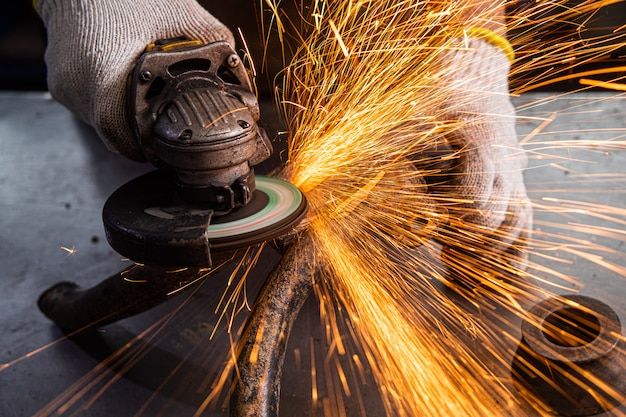 A young man welder in a blue gloves grinder metal an angle grinder   in the   workshop, sparks fly to the side