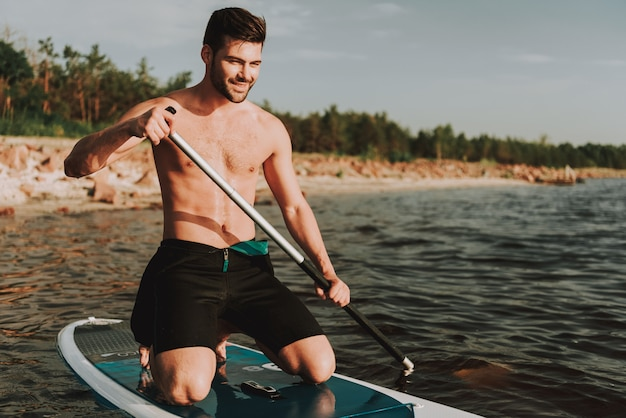 Young man in wetsuit rowing surf with paddle.