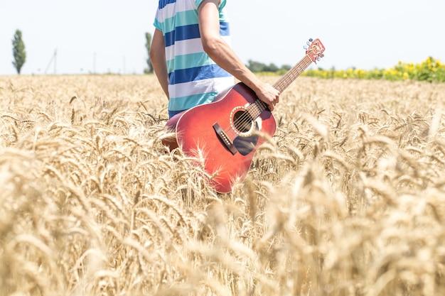 Giovane uomo in un campo di grano con una chitarra