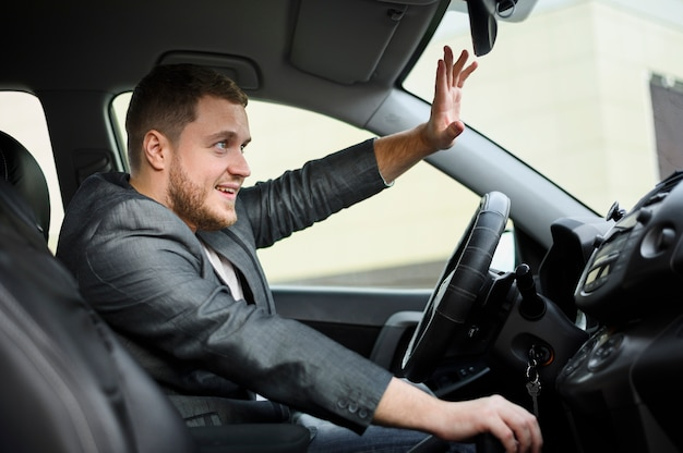 Young man at the wheel greeting someone