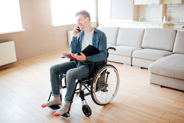 Young man in wheelchair. person with special needs. disability. student sitting and talking on phone. holding opened book in hands.