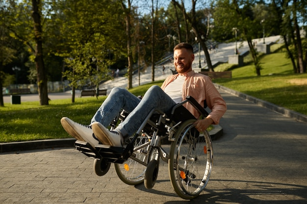 Young man in wheelchair shows his skill. paralyzed people and disability, handicap overcoming. disabled male person walking in park