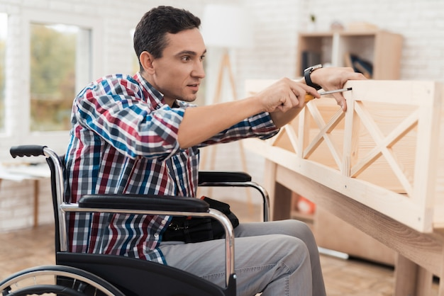 Young man in wheelchair tries himself to fold his bookcase